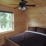 Comfortable beds in rustic log cabins